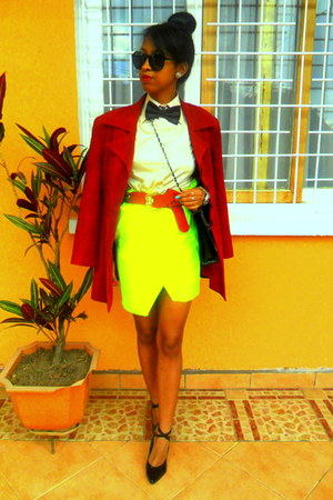 neon fabric worn as a skirt - ruby red coat - black bow tie - red belt