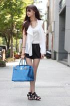 blue bag - black shorts - white vest