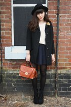 black coat - off white cable knit sweater - navy skirt - black lace-up wedges